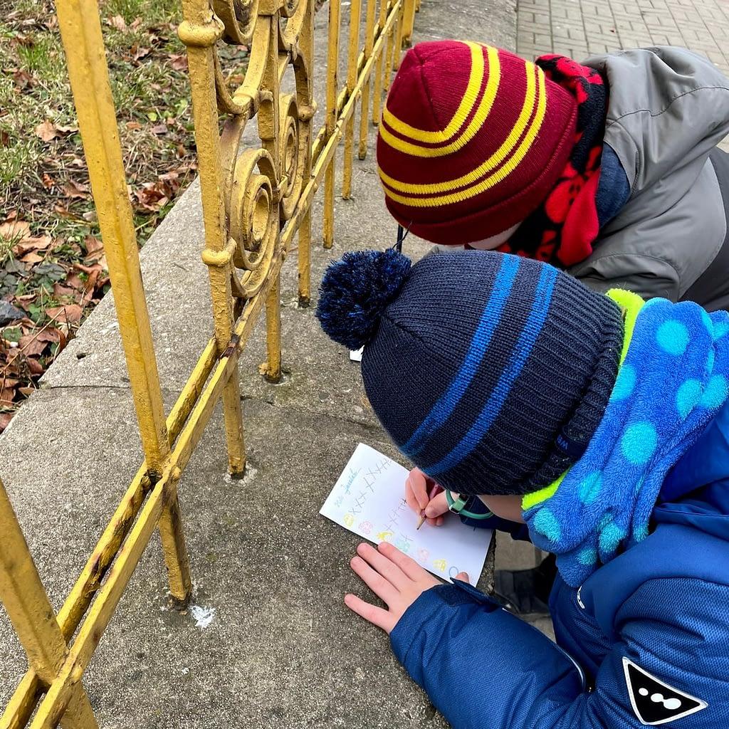 kluci zapisují opření o plot